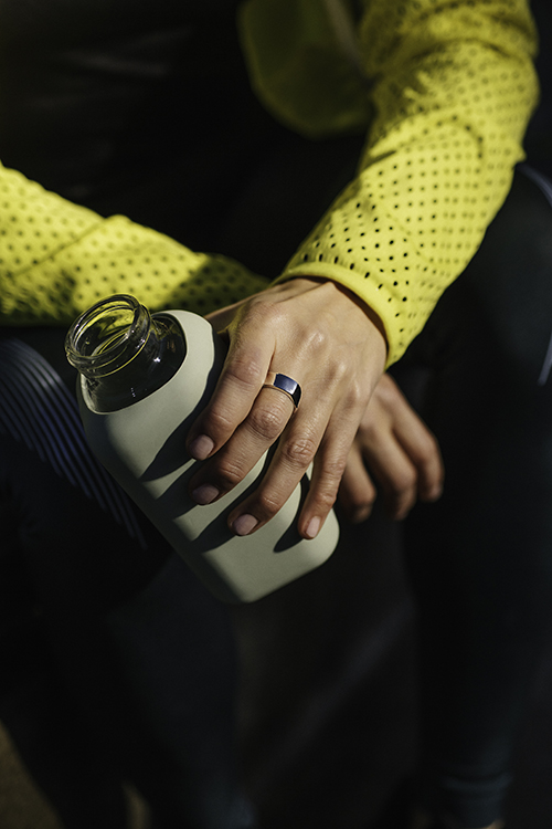 A woman holding a water bottle and wearing the Oura ring